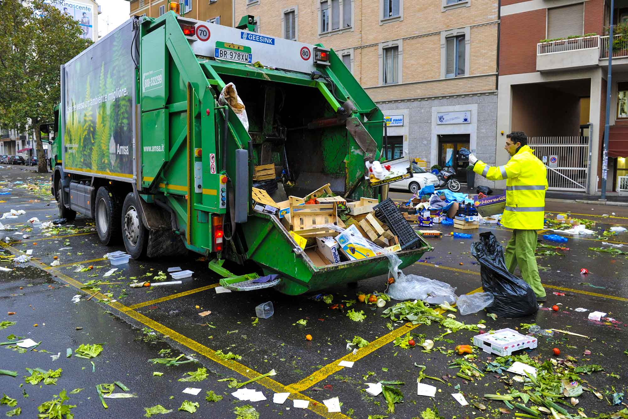Garbage truck in Milan after a food market
